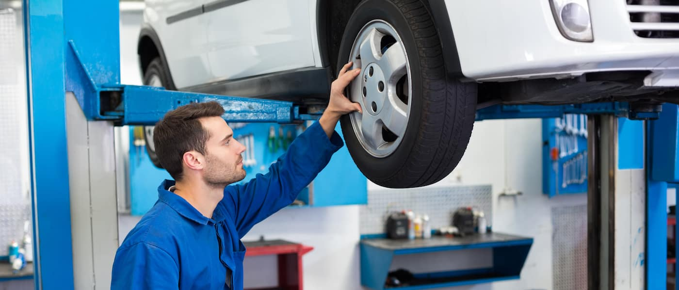 Service technician looking at tires on raised car