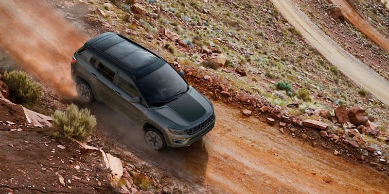 Black Jeep Compass driving down a dirt road