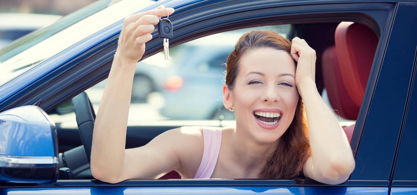 Woman smiling out of her car window holding car keys