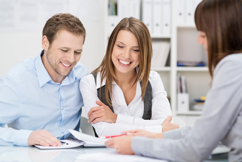 Couple looking at documents with finance advisor
