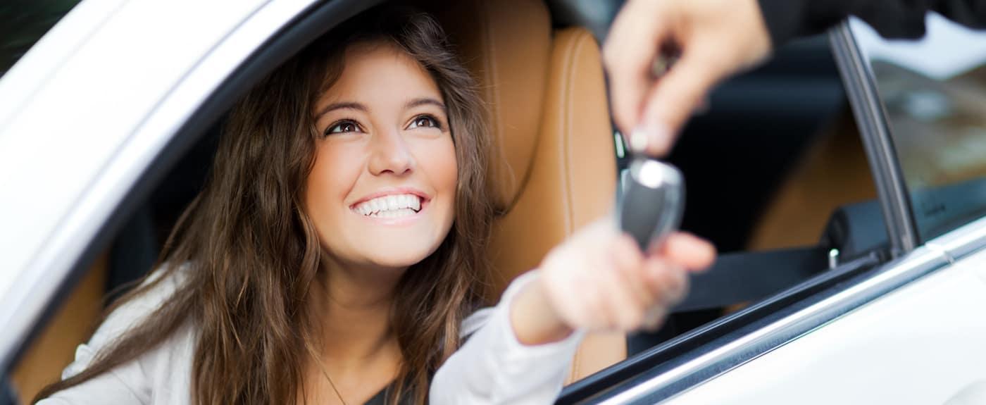 Woman sitting in car taking keys
