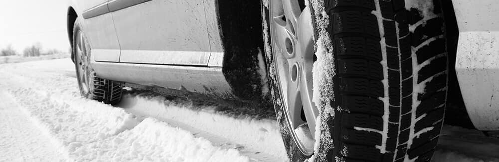 Closeup of vehicle tires on snowy road