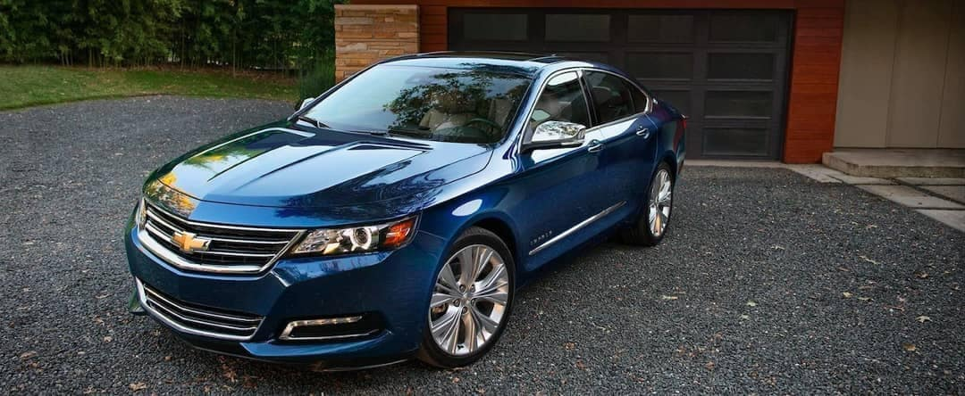 2018 Chevrolet Impala parked in front of garage door