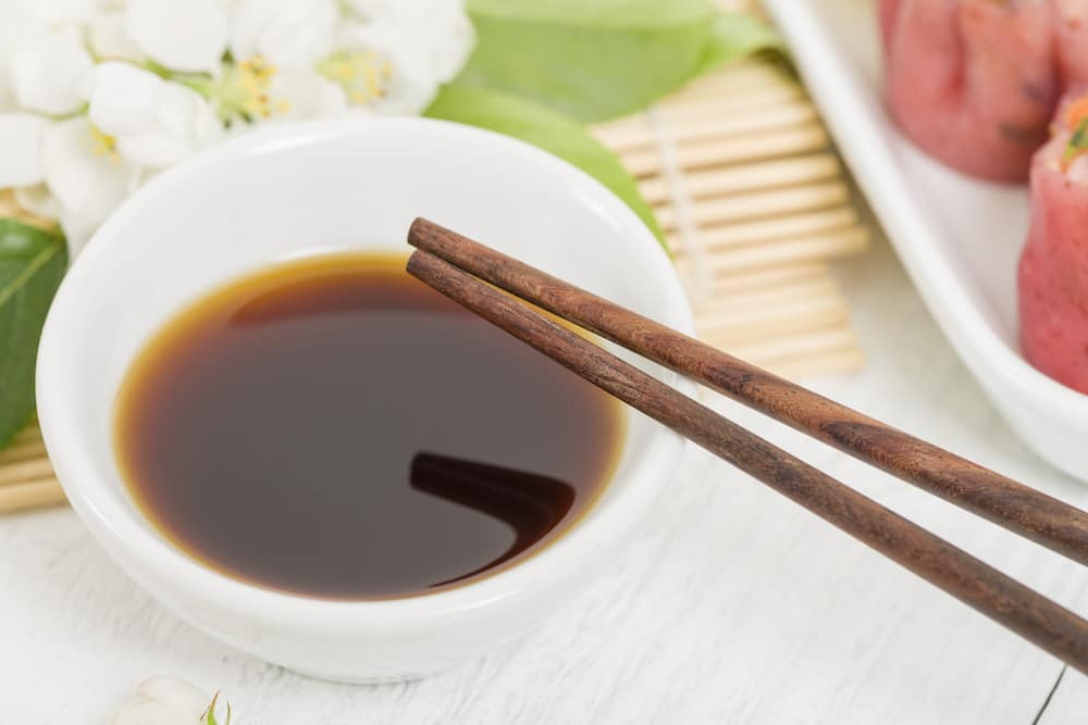 Soy dumpling sauce in white bowl with brown chop sticks