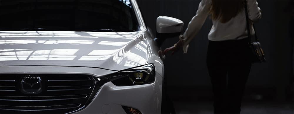 Woman getting into a Mazda SUV