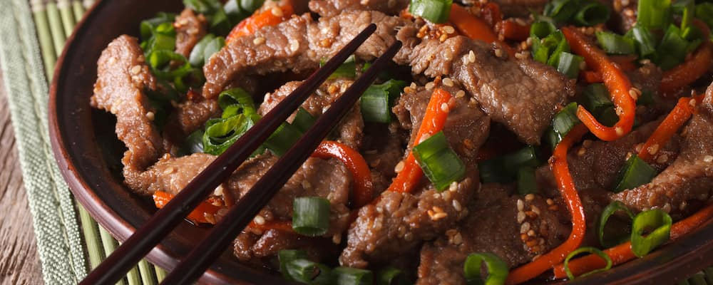 Asian food: slices of beef fried with sesame seeds and carrots closeup. horizontal
