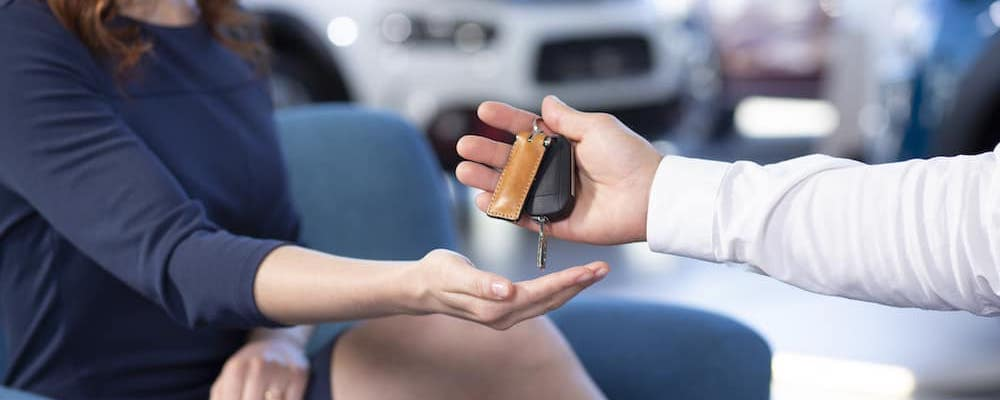 Dealership handing new car keys to woman in blue dress