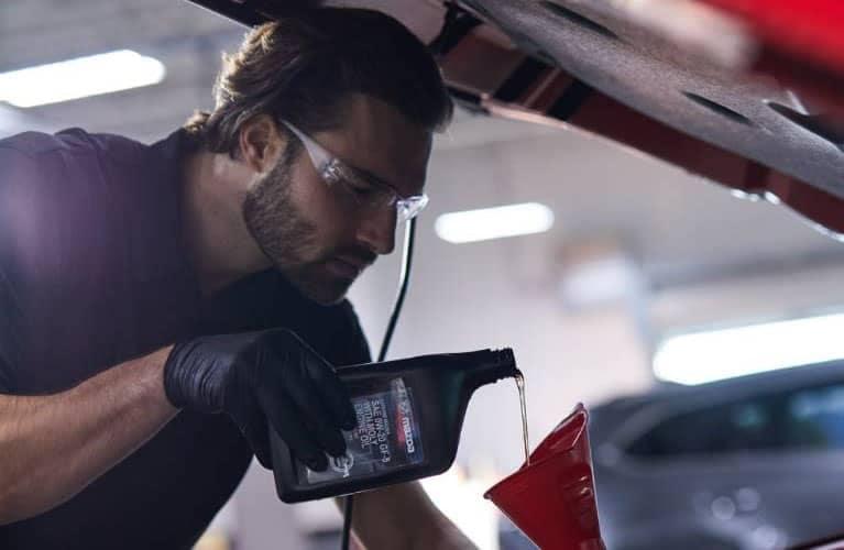 Mazda Mechanic Adding Engine Oil