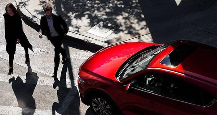 Couple walking by Mazda CX-5