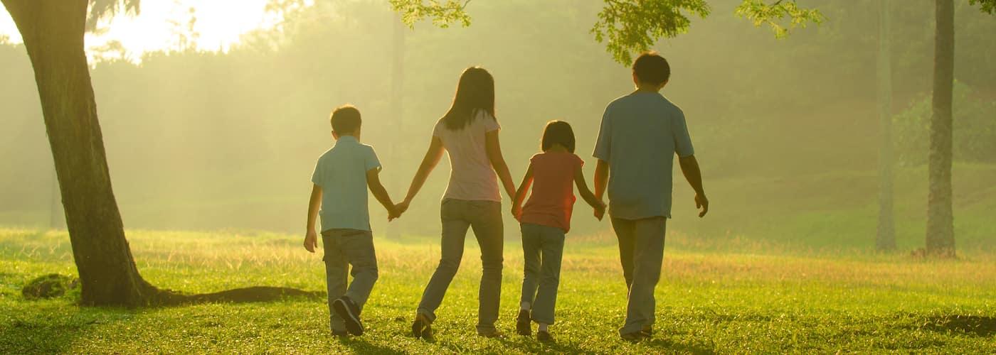 family walking through sunlit park