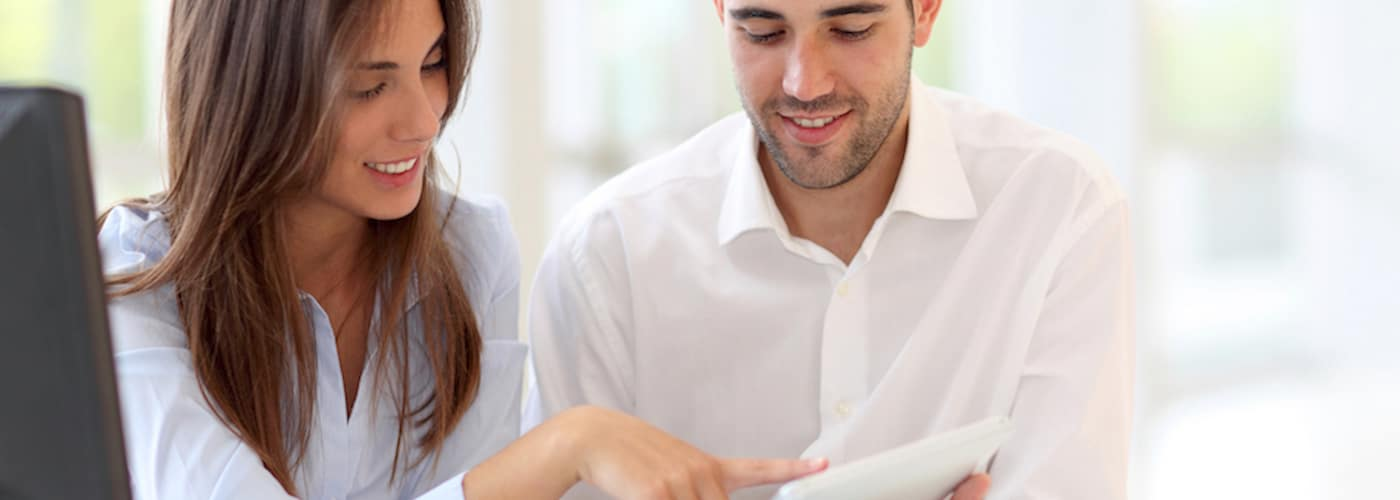 young couple looking at touchpad