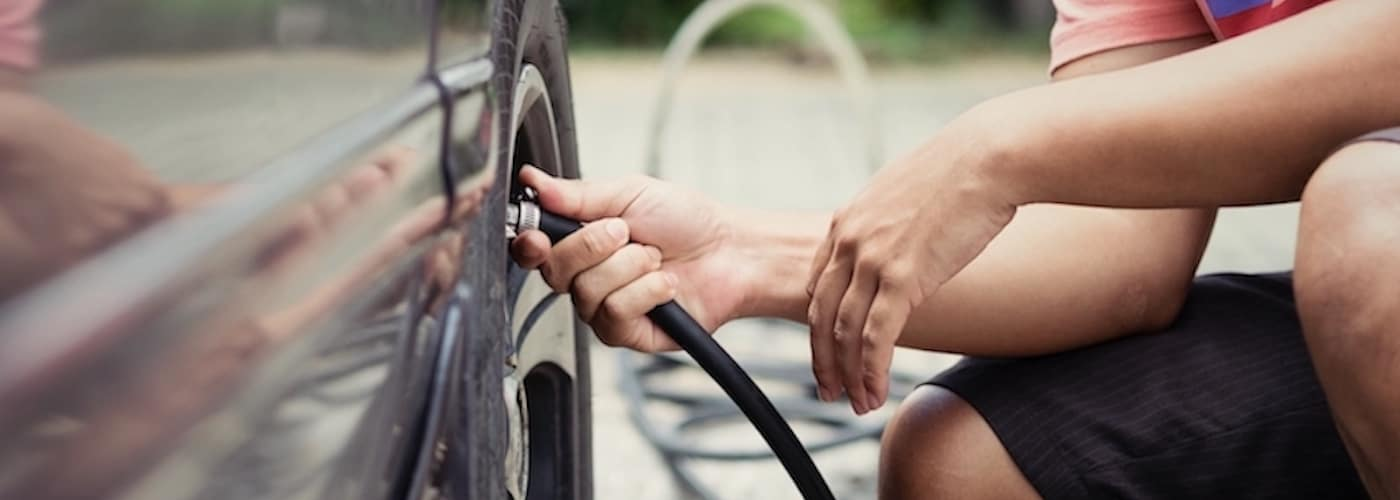 man checking tire pressure on car in driveway