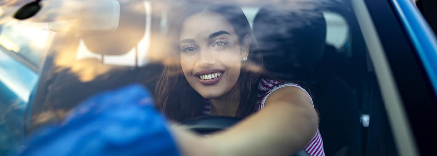 Young Woman Cleaning Car Windshield