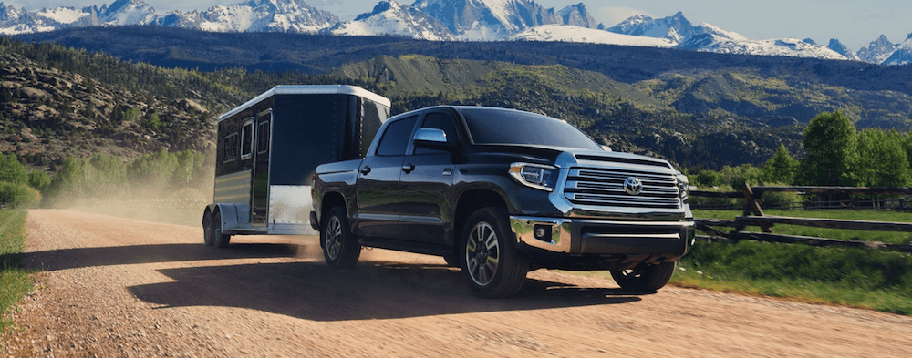 2020 Toyota Tundra towing trailer on rural mountain road