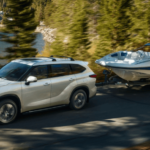 2021 Toyota Highlander Towing Boat on lakeside road