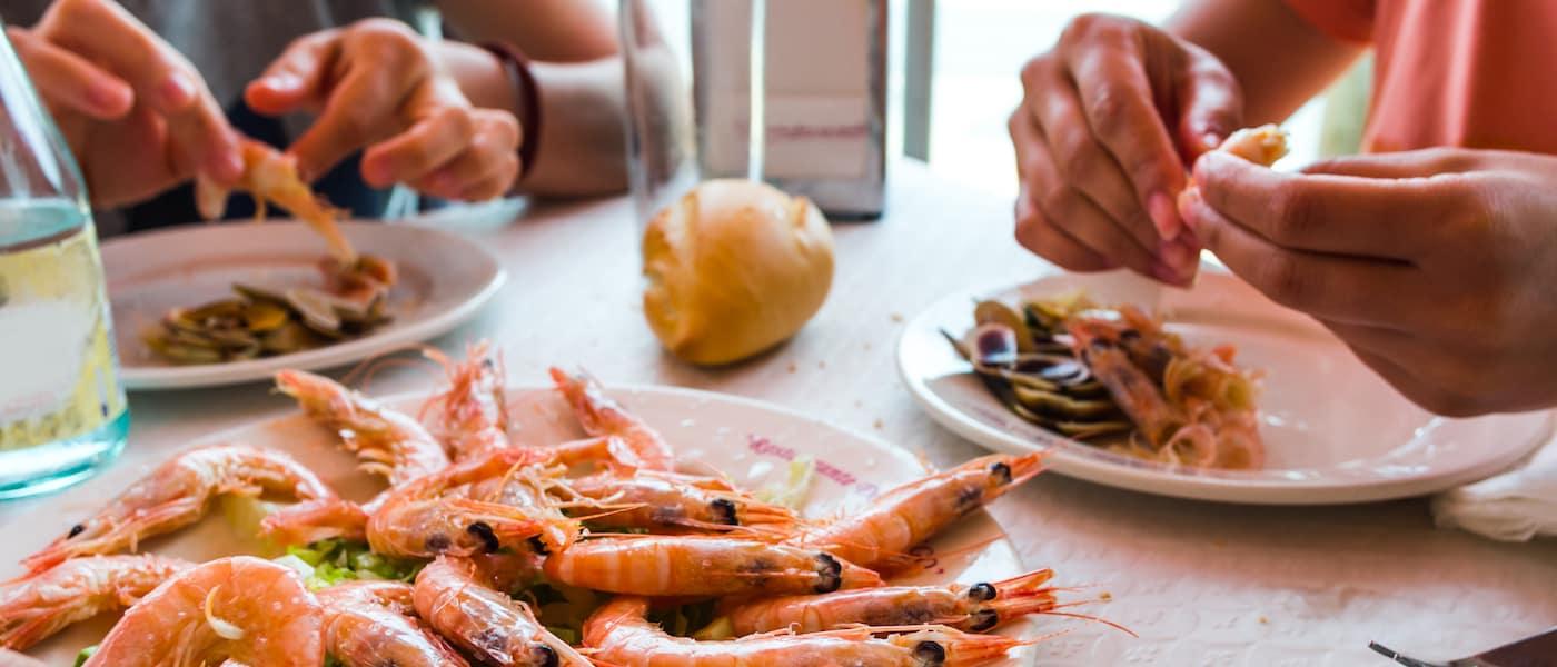 Friends in a restaurant eating shrimp
