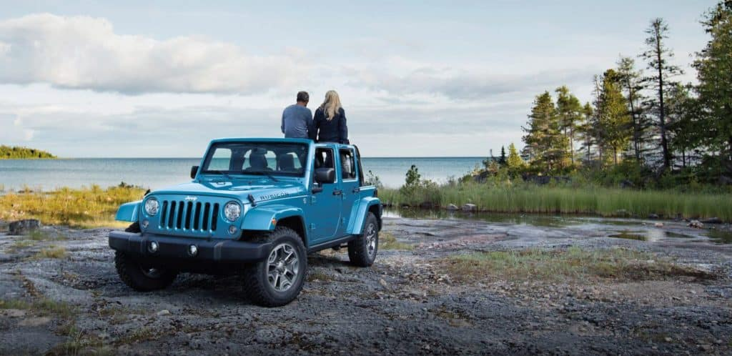 Jeep Wrangler JK parked off-road with couple leaning on it.