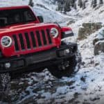 Jeep Wrangler driving up snowy cliffside