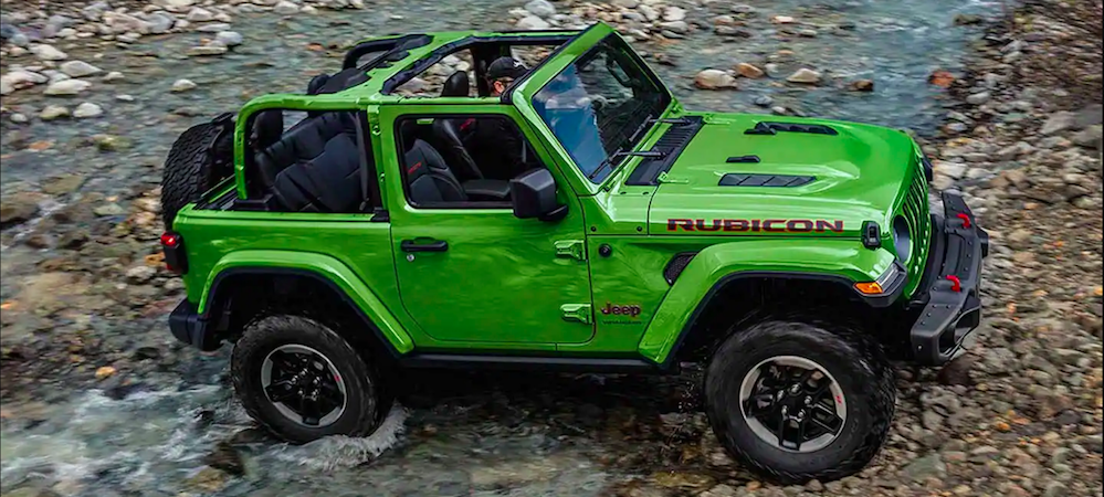 Bright green Wrangler parked on a rocky surface
