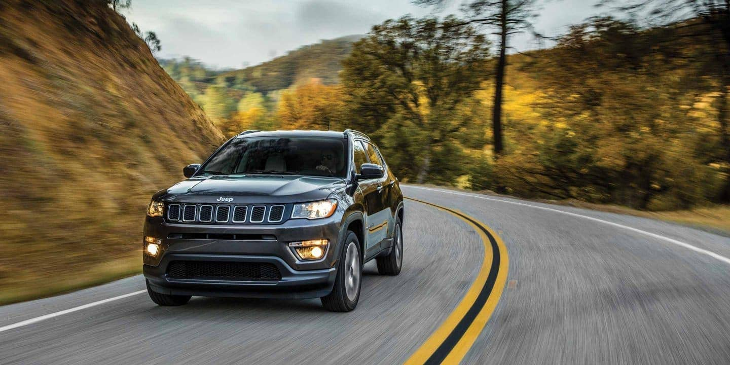 2019 Jeep Compass in charcoal driving down curved road