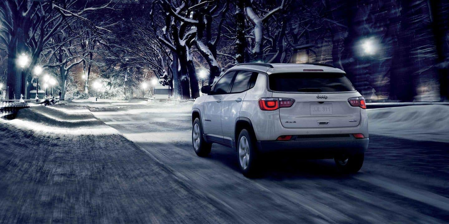 2019 Jeep Compass in white driving down snowy road