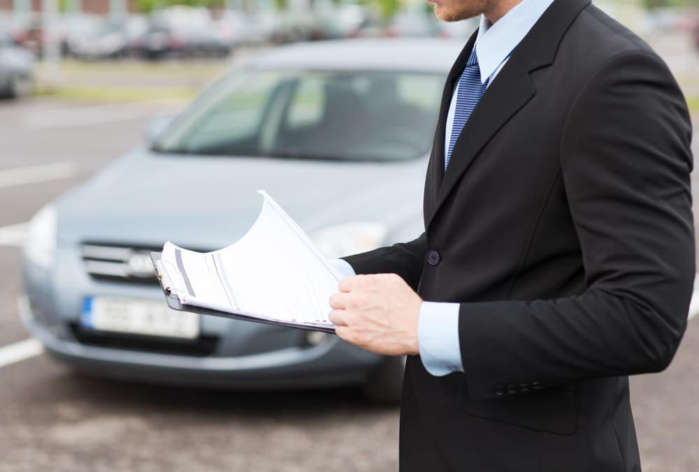 Man with paperwork by a car