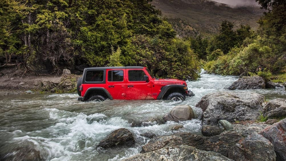 2019 Jeep Wrangler driving through rocky water